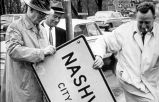 Photograph of Mayor Beverly Briley and others removing city limit sign, ca. 1962