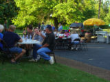 People eat by the Logan's Roadhouse tent in the River Plantation neighborhood during the May...