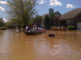 A man guides a rescue boat through the Pennington Bend neighborhood during the May 2010 flood