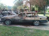 Lesli Bills's damaged car after flooding caused an explosion in her home during the May 2010...