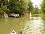 Michael Cain of the Harpeth River Watershed Association pulls a load of debris by kayak during a...