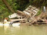 A volunteer approaches a pile of debris in her kayak during a river cleanup with the Harpeth River...