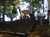 Volunteers drag the roof of a displaced shed up the riverbank during a Harpeth River Watershed...