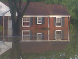 Lee and Amanda DeForest's flooded home in Madison is mirrored in the water during the May 2010...