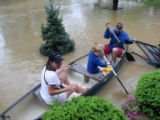 A family avoids a submerged basketball goal as they leave their home by canoe during the May 2010...