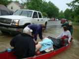 Volunteers pull a canoe of Bellevue residents to safety during the May 2010 flood