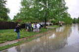 Bellevue residents talk together in a yard as water covers the street during the May 2010 flood