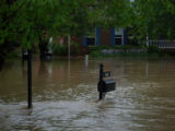 Water rushes around a mailbox during the May 2010 flood in Bellevue
