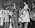 Photograph of mass meeting, Fisk University, Nashville, Tennessee, with Guy Carawan leading song...